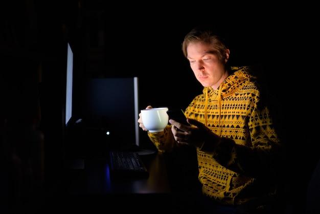 Giovane uomo bello che beve caffè e utilizza il telefono durante il lavoro straordinario a casa al buio