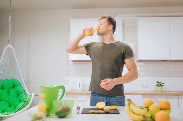 Giovane uomo bello che beve il succo di arancia fresco nella cucina. cibo salutare.