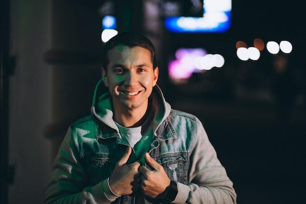 Giovane uomo bello che cammina alla sera fuori dalla strada