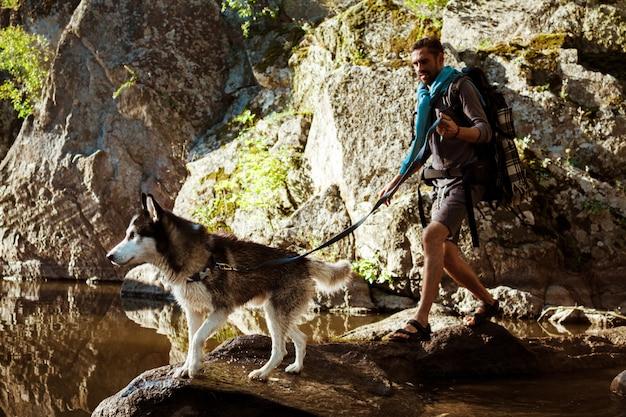 Giovane uomo bello che cammina con il cane husky nel canyon vicino all'acqua