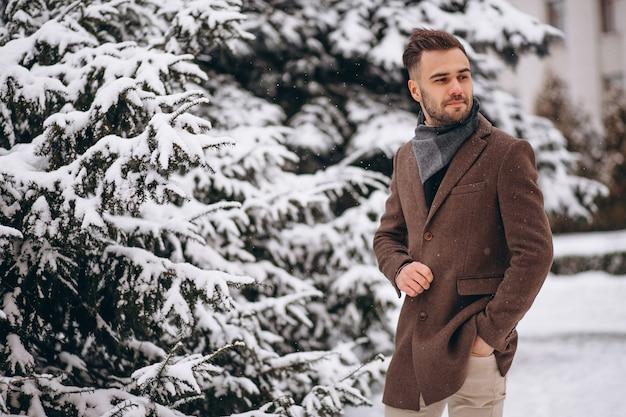 Giovane uomo bello che cammina in una foresta di inverno