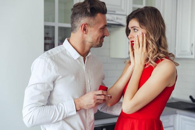 Giovane uomo bello che dà un anello di fidanzamento alla sua ragazza a casa