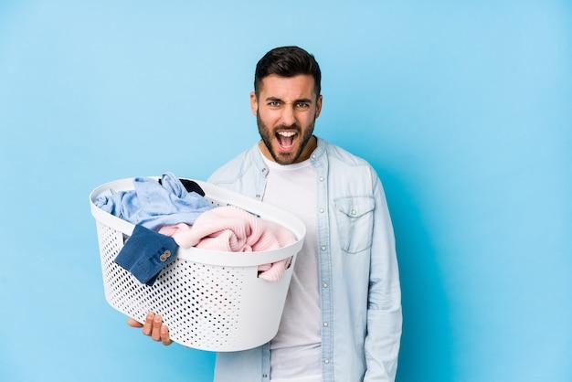 Giovane uomo bello che fa lavanderia isolato urlando molto arrabbiato e aggressivo.