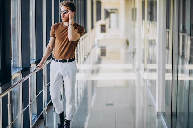 Giovane uomo bello che fa una pausa la finestra all'aeroporto