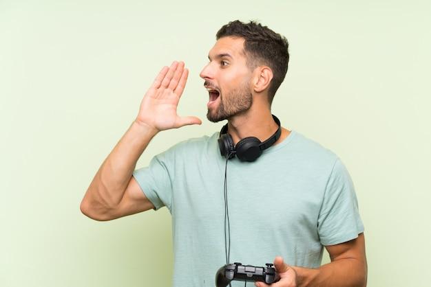 Giovane uomo bello che gioca con un controller di videogioco che grida con la bocca spalancata