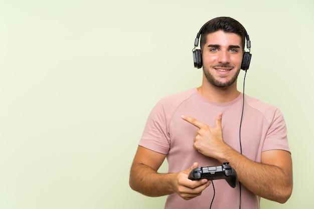 Giovane uomo bello che gioca con un controller di videogioco sul muro verde che punta verso il lato per presentare un prodotto