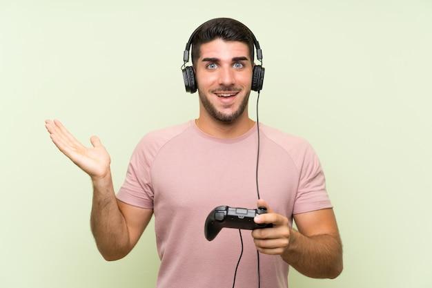 Giovane uomo bello che gioca con un controller di videogioco sul muro verde isolato con espressione facciale scioccata