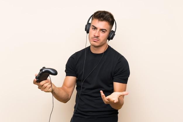 Giovane uomo bello che gioca con un controller di videogioco sul muro