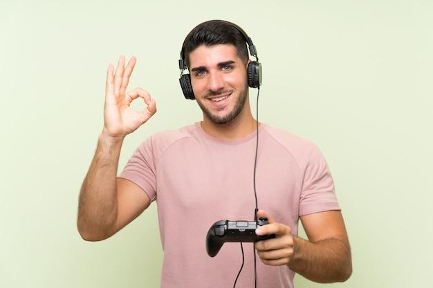 Giovane uomo bello che gioca con un controller di videogioco sulla parete verde che mostra il segno giusto con le dita