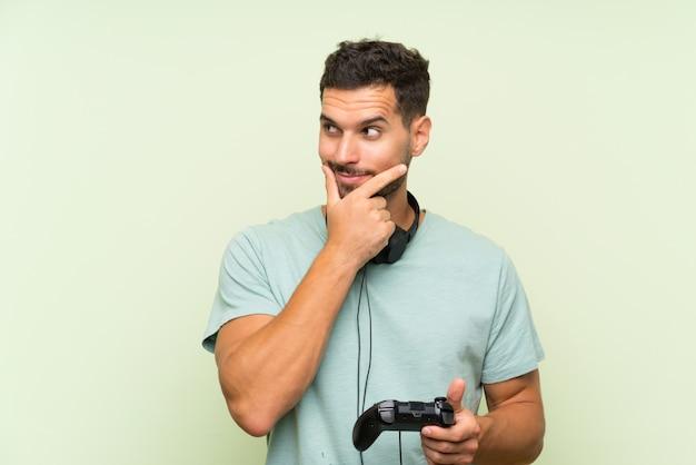 Giovane uomo bello che gioca con un controller e un pensiero del videogioco