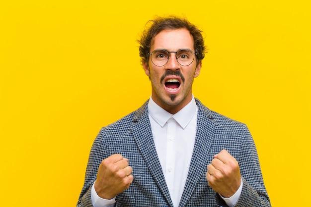 Giovane uomo bello che grida aggressivamente con lo sguardo infastidito, frustrato, arrabbiato e pugni stretti, sentendosi furioso contro la parete arancione