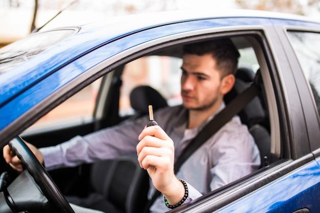 Giovane uomo bello che guida la sua nuova auto, tendendo le chiavi