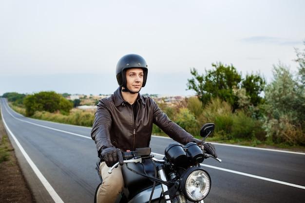Giovane uomo bello che guida su una moto a strada di campagna.