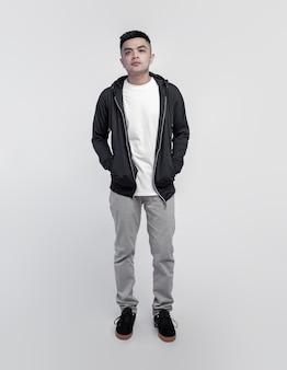 Giovane uomo bello che indossa felpa con cappuccio nera e maglietta bianca isolata sullo spazio