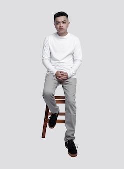 Giovane uomo bello che indossa la maglietta bianca a maniche lunghe è seduto su una sedia