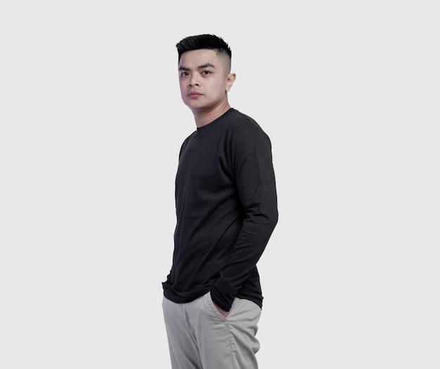 Giovane uomo bello che indossa la maglietta nera a maniche lunghe isolata su bianco