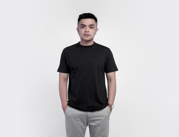 Giovane uomo bello che indossa la maglietta nera isolata su bianco