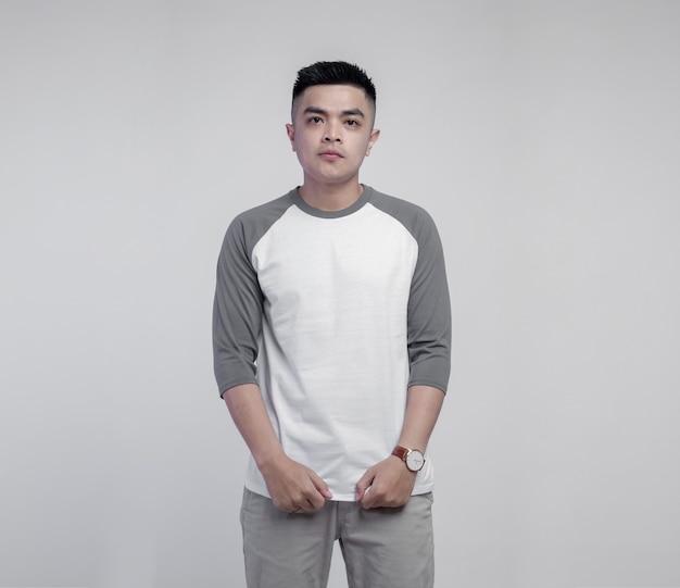 Giovane uomo bello che indossa la maglietta raglan grigia bianca isolata sullo spazio