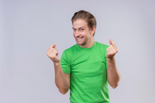Giovane uomo bello che indossa la maglietta verde che fa gesto di soldi