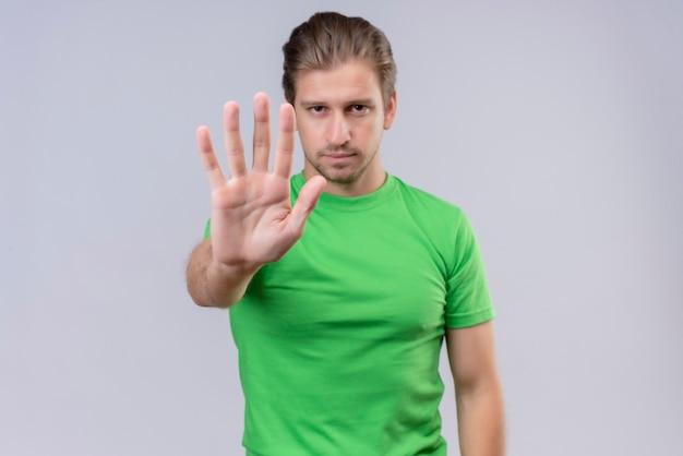 Giovane uomo bello che indossa la maglietta verde che fa il fanale di arresto con la mano aperta