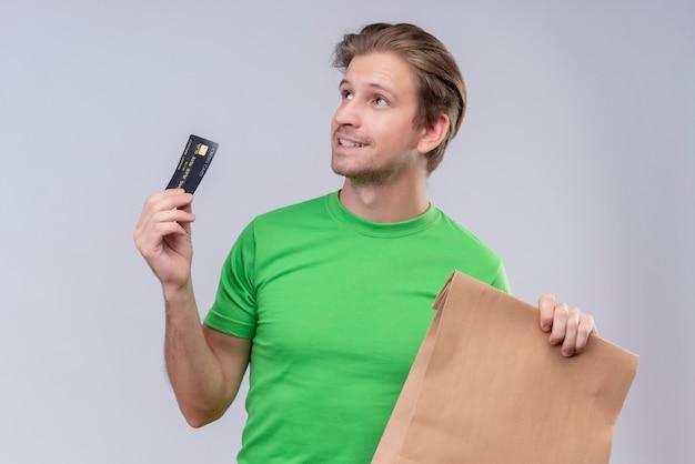 Giovane uomo bello che indossa la maglietta verde che tiene il pacchetto di carta e la macchina di credito che osserva in su