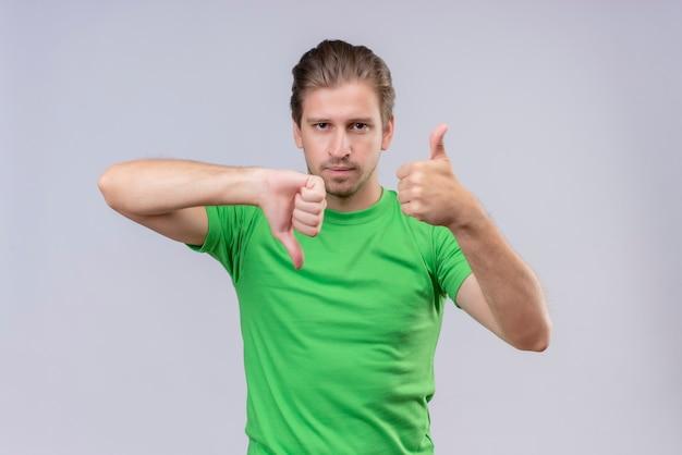 Giovane uomo bello che indossa la maglietta verde con un'espressione seria sul viso