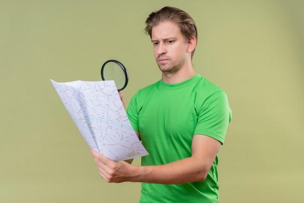 Giovane uomo bello che indossa la maglietta verde guardando la mappa attraverso la lente di ingrandimento con un'espressione seria sul viso in piedi sopra la parete verde