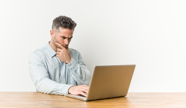Giovane uomo bello che lavora con il suo computer portatile che guarda lateralmente con l'espressione dubbiosa e scettica.