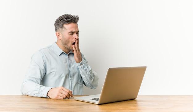 Giovane uomo bello che lavora con il suo computer portatile che sbadiglia mostrando una bocca stanca della copertura di gesto.