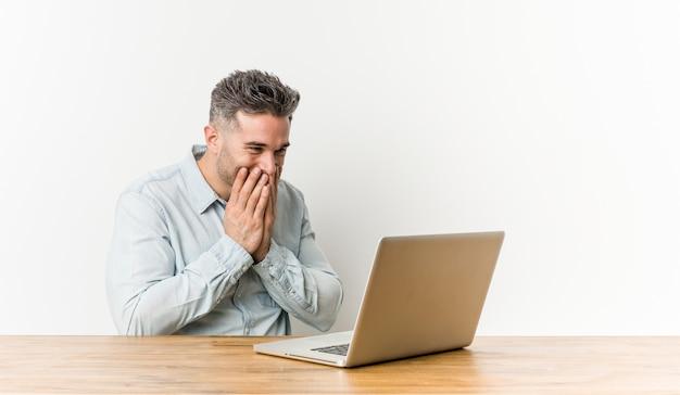 Giovane uomo bello che lavora con il suo laptop ridendo di qualcosa, coprendo la bocca con le mani.
