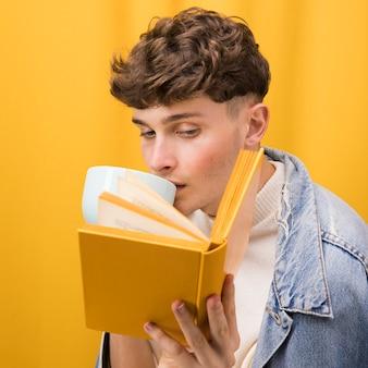 Giovane uomo bello che legge un libro in una scena gialla