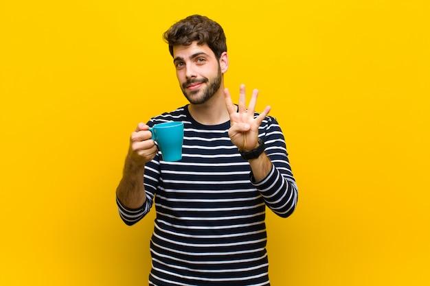 Giovane uomo bello che mangia un caffè