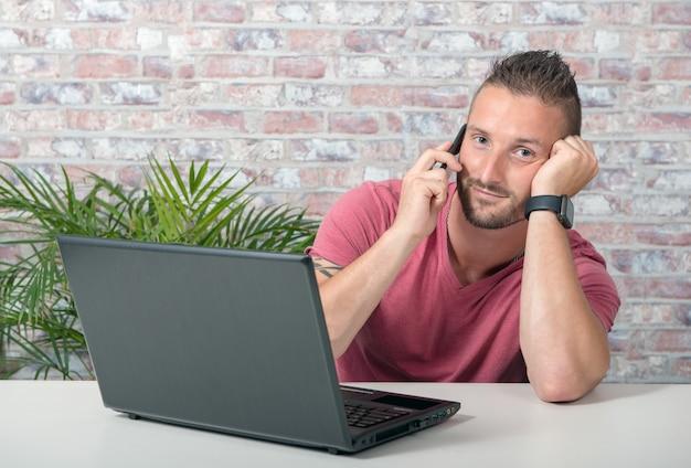 Giovane uomo bello che parla sul telefono in ufficio