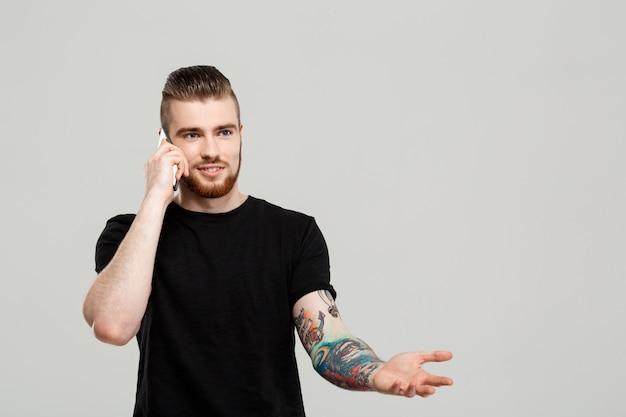 Giovane uomo bello che parla sul telefono sopra la parete grigia.