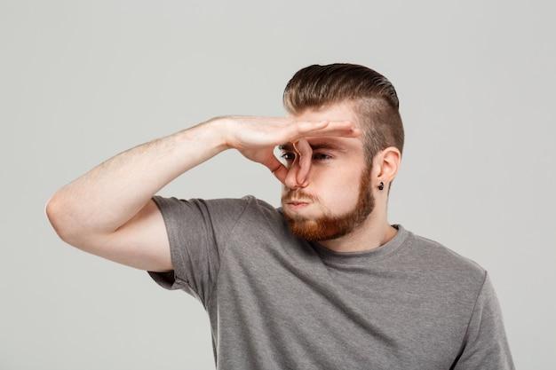 Giovane uomo bello che pizzica naso sopra la parete grigia.