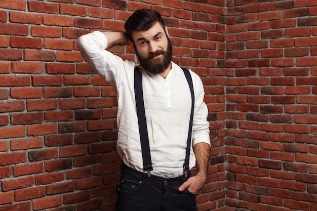 Giovane uomo bello che posa sul muro di mattoni.