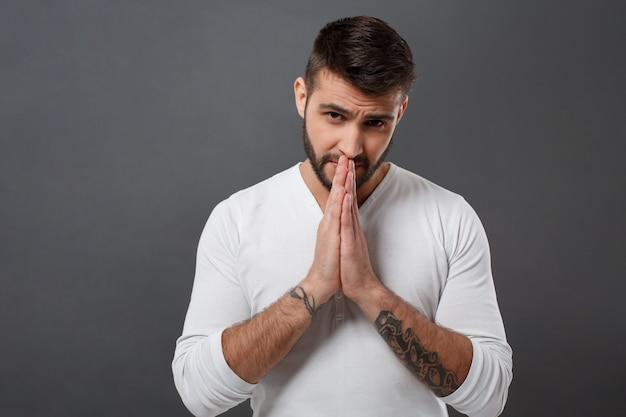 Giovane uomo bello che prega sopra la parete grigia