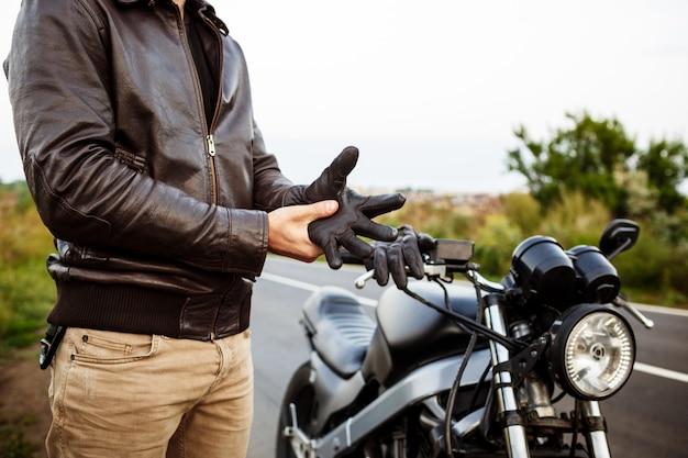 Giovane uomo bello che propone vicino alla sua moto, indossando guanti.