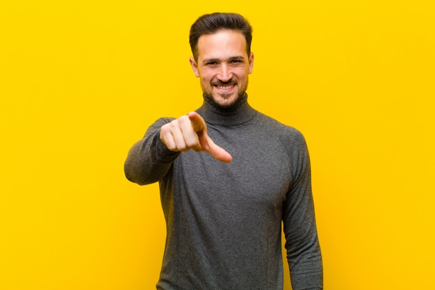 Giovane uomo bello che punta alla fotocamera con un sorriso soddisfatto, fiducioso, amichevole, scegliendola contro il muro arancione