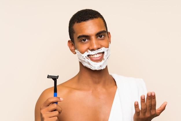 Giovane uomo bello che rade la sua barba che invita a venire con la mano