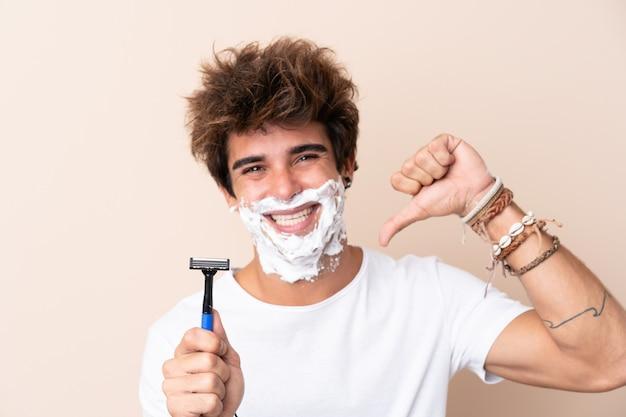 Giovane uomo bello che rade la sua barba fiera e soddisfatta di sé