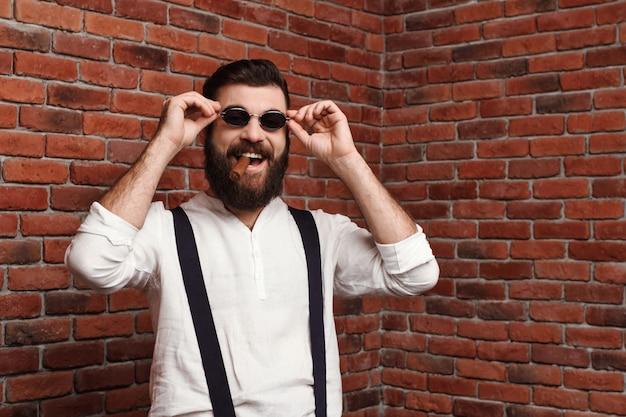 Giovane uomo bello che ride tenendo il sigaro sul muro di mattoni.