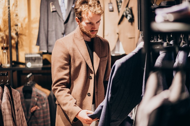 Giovane uomo bello che sceglie i vestiti al negozio