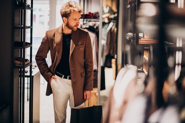 Giovane uomo bello che sceglie panno al negozio