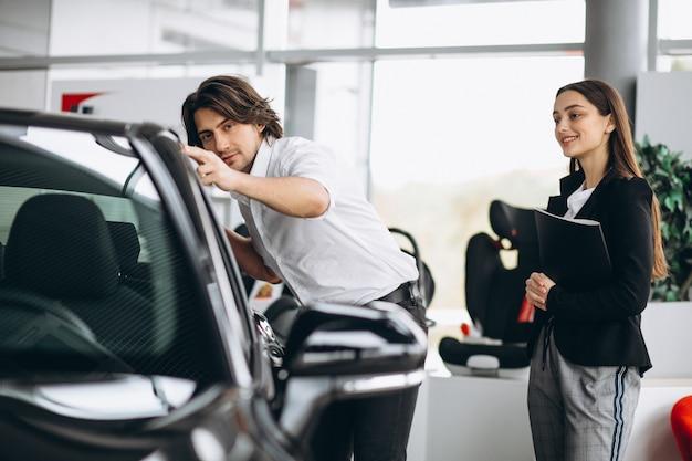 Giovane uomo bello che sceglie un'automobile in una sala d'esposizione dell'automobile