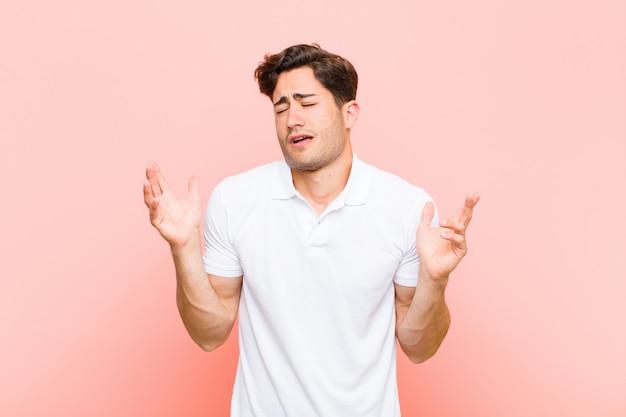 Giovane uomo bello che scrolla le spalle con un'espressione stupida, pazza, confusa, perplessa, sentendosi infastidita e all'oscuro su sfondo rosa