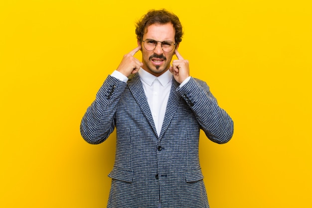 Giovane uomo bello che sembra arrabbiato, stressato e infastidito, che copre entrambe le orecchie a un rumore assordante, suono o musica ad alto volume sulla parete arancione