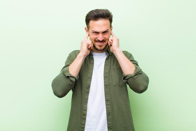 Giovane uomo bello che sembra arrabbiato, stressato e infastidito, coprendo entrambe le orecchie con un rumore assordante, suono o musica ad alto volume