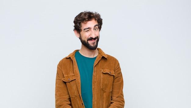 Giovane uomo bello che sembra felice e amichevole, sorridente e ammiccante con un atteggiamento positivo contro il muro piatto