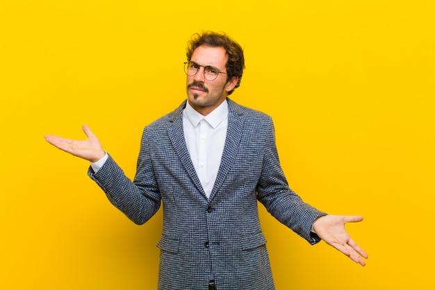 Giovane uomo bello che sembra perplesso, confuso e stressato, chiedendosi tra diverse opzioni, sentendosi incerto muro arancione